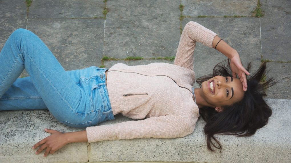 girl-lying-down-smiling-and-looking-in-the-sky